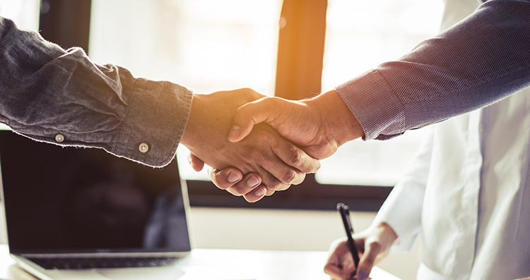 Two businessmen handshaking in meeting after final project agree